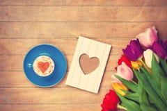 Cadre de tasse et de photo près des fleurs Image libre de droits