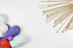 Cadre de tricotage de fond Paires d'aiguilles de tricotage en bois et de fil coloré sur le fond blanc Images stock