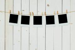 Cadre en blanc de la photo cinq accrochant sur le fond en bois blanc avec la station thermale photographie stock libre de droits