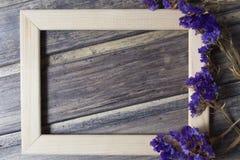 Cadre en bois avec la décoration bleue sèche de fleur sur la table en bois Photographie stock libre de droits