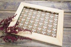 Cadre en bois avec la décoration sèche de fleur sur la table en bois Photos stock
