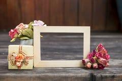 Cadre en bois avec la fleur de papier et le boîte-cadeau sur le plancher en bois Images stock
