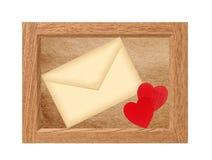 Cadre en bois avec la lettre d'amour d'isolement sur le blanc Photo stock
