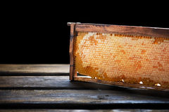 Cadre en bois avec le nid d'abeilles plein du miel, sur le noir Image stock