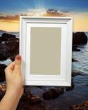Cadre en bois chez des mains de la femme sur le coucher du soleil de fond Photo stock