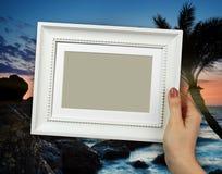 Cadre en bois chez des mains de la femme sur le coucher du soleil de fond Photos libres de droits