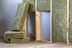 Cadre en bois pour de futurs murs avec des plats de cloison sèche isolés avec le personnel d'isolation de laine et de fibre de ve photos stock