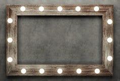 Cadre en bois sur le fond concret illuminé par les ampoules Photographie stock