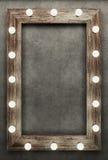 Cadre en bois sur le fond concret illuminé par les ampoules Photo stock