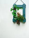 Cadre en bois vert avec du raisin en céramique animal de poupée et feuille verte Images stock