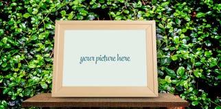 Cadre en bois vide de photo sur l'herbe pour la moquerie  Photographie stock libre de droits
