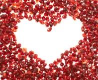 Cadre en forme de coeur des graines de grenade Photos stock