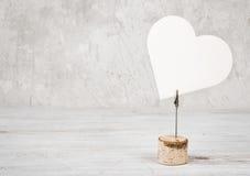 Cadre en forme de coeur vide sur la table en bois contre le mur de vintage Photo libre de droits