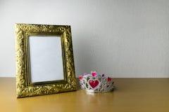 Cadre et couronne de photo sur la table en bois photographie stock libre de droits