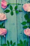Cadre floral de roses roses romantiques sur le gris, fond en bois peint Photo libre de droits