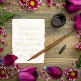 Cadre floral des fleurs roses et de la carte de papier avec la calligraphie et stylo sur le fond en bois Configuration plate, vue Image stock