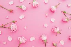 Cadre floral fait de fleurs et pétales de roses sur le fond rose Configuration plate, vue supérieure Fond de jour de valentines Photographie stock libre de droits