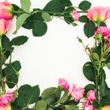 Cadre floral fait de roses, bourgeons et feuilles de vert sur le fond blanc Configuration plate, vue supérieure Fond de source Photo libre de droits