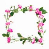 Cadre floral fait de roses, branches et feuilles roses sur le fond blanc Configuration plate, vue supérieure Composition en Heart Photos libres de droits