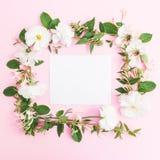Cadre floral fait en fleurs blanches et carte de papier sur le fond rose Fond floral Configuration plate, vue supérieure Photos stock