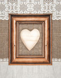 Cadre âgé avec le coeur en bois sur la toile de jute Photographie stock libre de droits