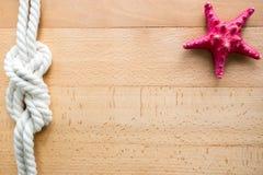 Cadre horizontal de voyage en mer avec les étoiles de mer rouges et le noeud marin Photo stock