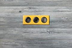 Cadre jaune lumineux triple avec la prise de puissance, les ports d'usb et le commutateur principal léger sur le mur en bois gris photographie stock libre de droits