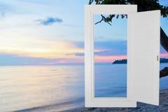 Cadre ouvert blanc de fenêtre avec le fond de plage de coucher du soleil Images stock