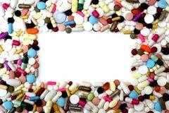 Cadre rectangulaire des pilules colorées sur le fond blanc Images stock