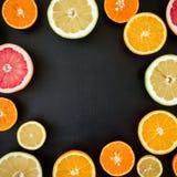 Cadre rond des oranges, du pamplemousse et du citron d'isolement sur le fond noir Configuration plate, vue supérieure Mélange tro Photographie stock libre de droits