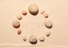 Cadre rond des pierres de mer avec le lettrage d'été dessiné sur le sable Image libre de droits