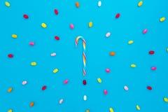 Cadre rond fait de canne à sucre colorée lumineuse de sucrerie et d'arc-en-ciel sur le fond bleu Configuration plate, vue supérie Image stock