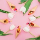 Cadre rond fait de sucrerie lumineuse colorée en cônes de gaufre et fleurs blanches sur le fond rose Configuration plate, vue sup Photos libres de droits