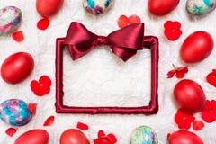 Cadre rouge vide et oeufs de pâques peints Photographie stock