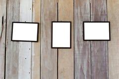 Cadre trois en blanc sur le mur en bois Photographie stock