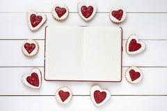Cadre vide de carnet pour le texte de conception et les biscuits en forme de coeur sur le fond en bois blanc Image stock