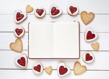 Cadre vide de carnet pour le texte de conception et les biscuits en forme de coeur sur le fond en bois blanc Photo stock