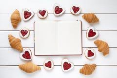 Cadre vide de carnet pour le texte de conception, les croissants et la composition en forme de coeur en biscuits le jour de valen Photos libres de droits