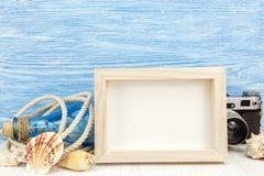 Cadre vide de photo, coquillages, bouteille et appareil-photo classique sur le bleu Image stock
