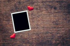 Cadre vide de photo et coeur rouge sur le fond en bois avec l'espace Photographie stock