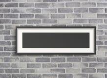 Cadre vide sur le mur gris de birck Photographie stock