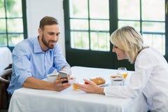 Cadres à l'aide du téléphone portable dans un restaurant Photos libres de droits