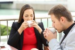 Cadres buvant des tasses de café dans une terrasse de barre images libres de droits