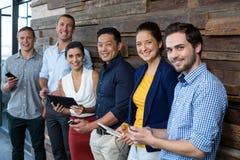 Cadres commerciaux de sourire à l'aide du téléphone portable et du comprimé numérique dans le bureau Photos stock