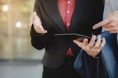 Cadres commerciaux utilisant la Tablette de Digital en dehors du bureau photo stock