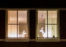 Cadres de fenêtre avec des décorations de lumière de Noël derrière elles photographie stock