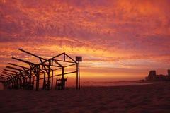 Cadres de hutte de plage silhouettés contre le ciel rouge vif de coucher du soleil avec les nuages dramatiques photo stock