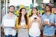 Cadres de sourire à l'aide de l'ordinateur portable, du téléphone portable et du comprimé numérique Photographie stock libre de droits