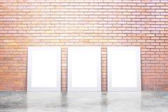 Cadres de tableau blancs vides sur le plancher en béton et le mur de briques rouge, Photos stock