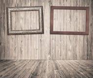 Cadres de tableau en bois accrochant sur le mur gris de planches Images libres de droits
